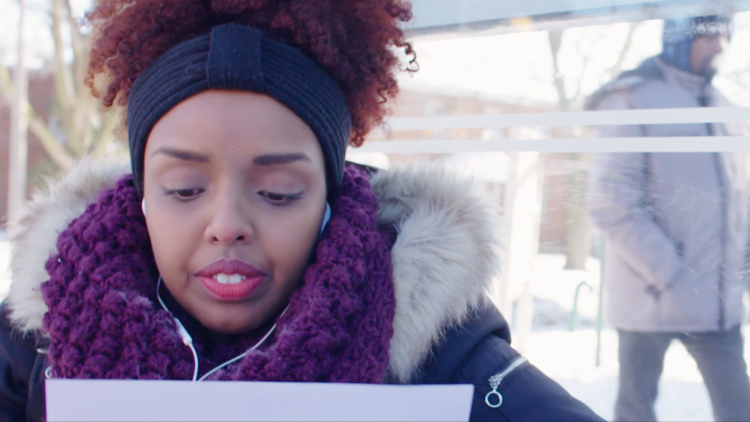 virgins! the series, Amina the apprehensive queer virgin, is looking at a rejection letter for a grant in a bus shelter